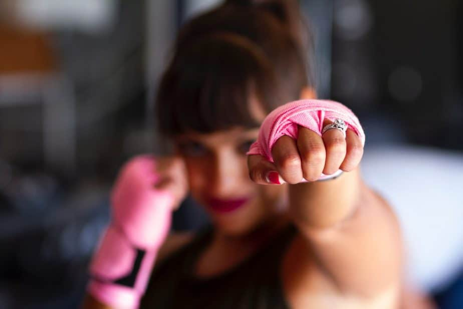 Femme de poinçonnage avec des gants de cancer du sein rose