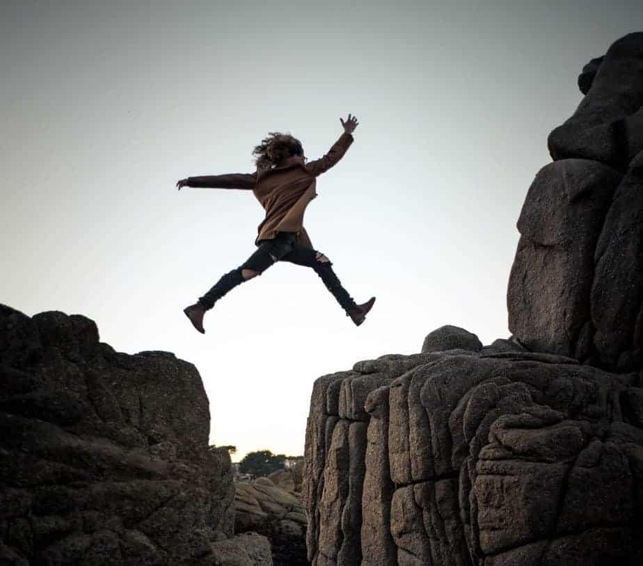 Девушка прыгает через каньон, рискованное поведение