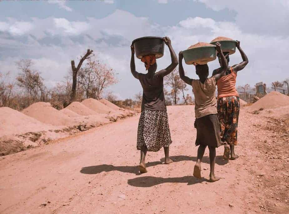 Photo of three women carrying basin while walking barefoot