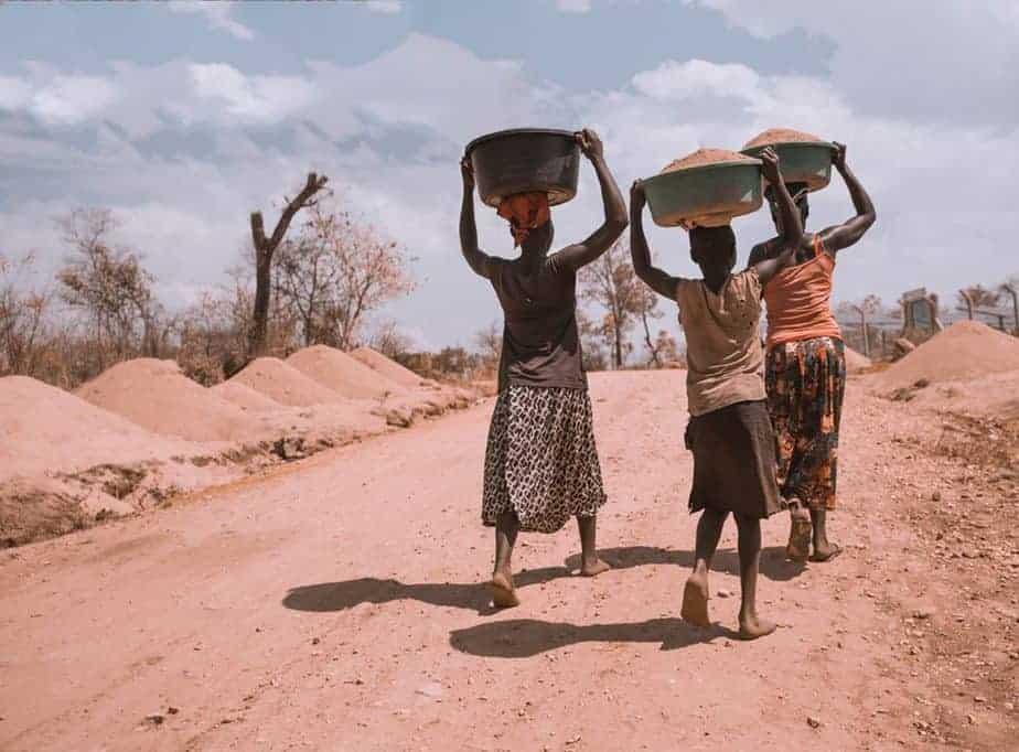 Foto von drei Frauen, die Becken tragen, während sie barfuß gehen