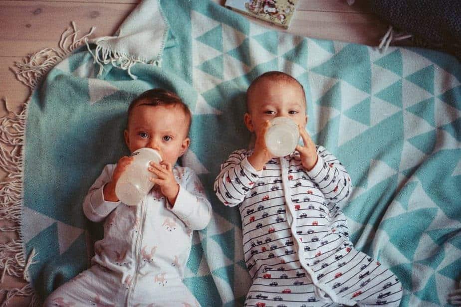 Zwillingsbabys, die auf blaugrüner Decke liegen