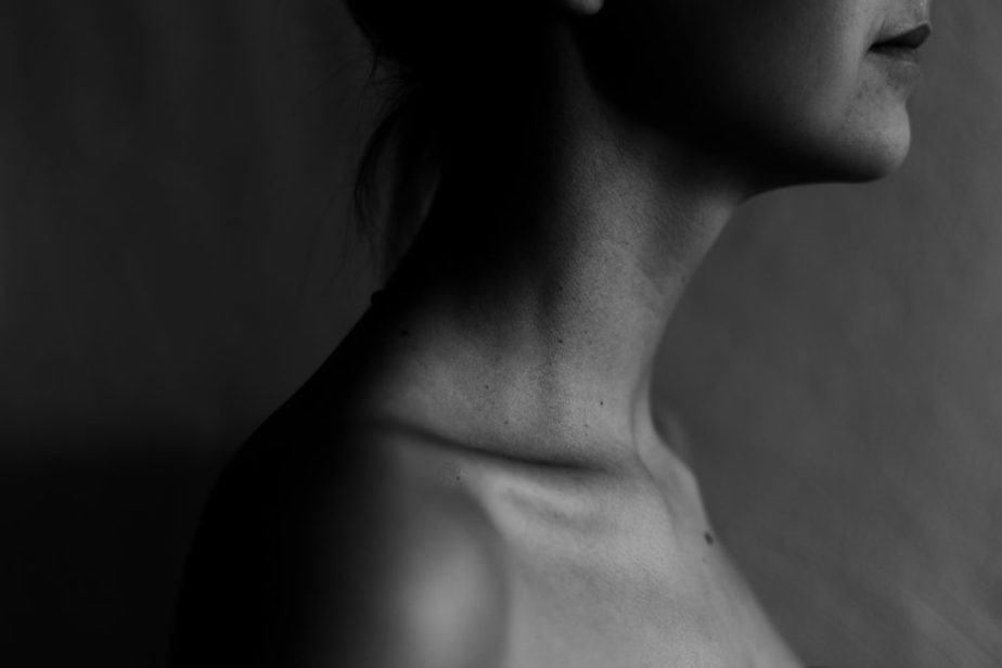 Fotografía en escala de grises de la garganta de la mujer.