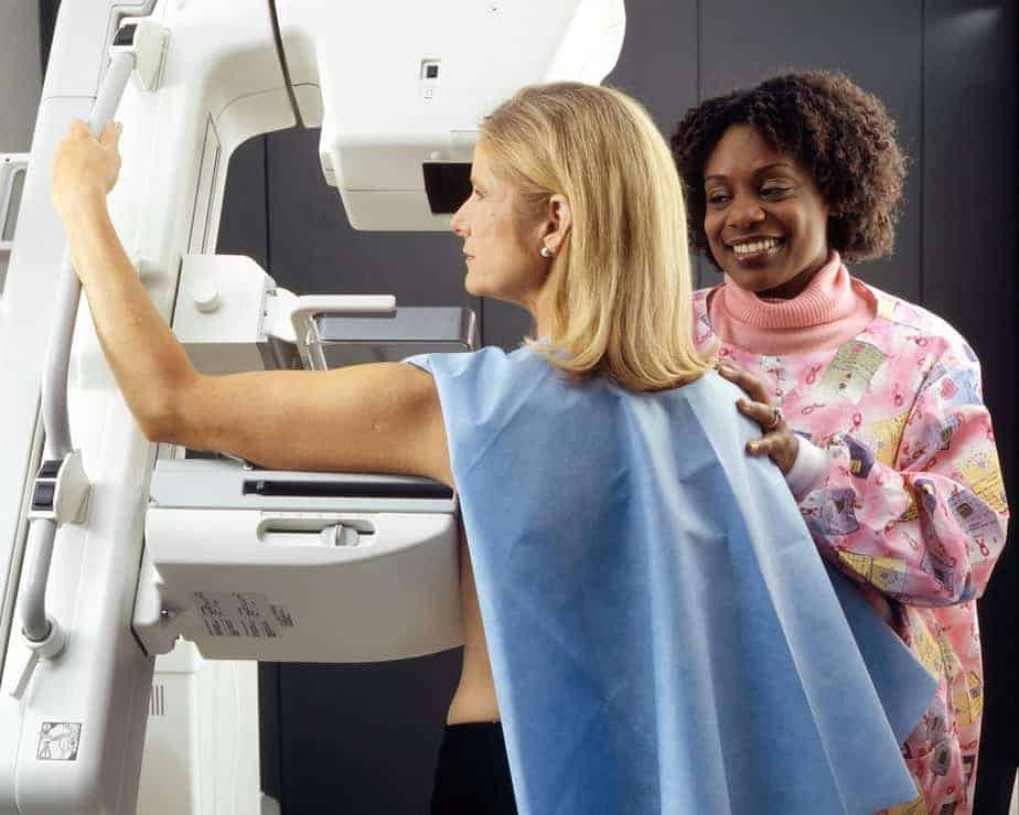 breast cancer screening woman standing near another woman beside mammogram machine