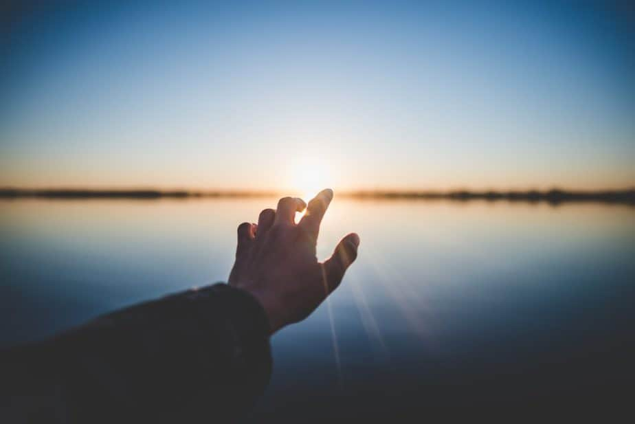 mano izquierda tendida hacia el cielo