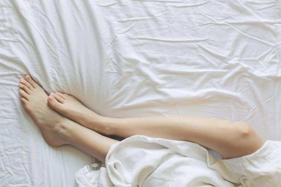 спит на кровати, показывая ноги