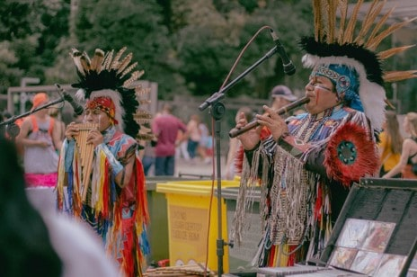 Two Native Americans Playing Woodwind Instruments