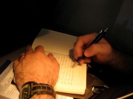 Someone writing in a sleep diary